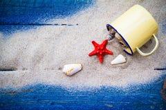 Kolorowy piasek posypywać skorupy filiżanki błękita deski Fotografia Stock