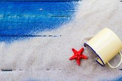 Kolorowy piasek posypywać skorupy filiżanki błękita deski Zdjęcia Royalty Free