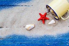 Kolorowy piasek posypywać skorupy filiżanki błękita deski Obraz Stock