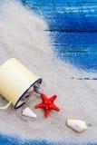 Kolorowy piasek posypywać skorupy filiżanki błękita deski Zdjęcie Royalty Free