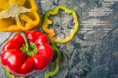 Kolorowy pieprz czerwieni zieleni koloru żółtego zakończenie w górę odgórnego widoku na zmroku kamieniu fotografia stock