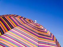 Kolorowy plażowy parasol przeciw niebieskiemu niebu pasiasta tekstura Fotografia Stock