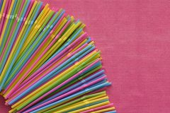 Kolorowy pojedynczy używa rozporządzalne plastikowe słoma w kącie na różowi powierzchnię fotografia stock