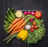 Kolorowy różnorodny organicznie rolni warzywa w drewnianym pudełku na drewnianym nieociosanym tło odgórnego widoku zakończeniu up fotografia royalty free