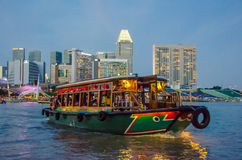 Kolorowy riverboat pływa statkiem w schronieniu przy zmierzchem z miasto linią horyzontu w tle Zdjęcie Stock
