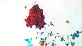 Kolorowy suchy atrament poruszający na bielu mleka tle, odgórny widok Zakończenie dla w górę prochowej farby unosi się na powierz zdjęcie royalty free