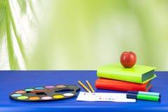 Kolorowy szkolny wyposażenie i dwa książki na zmroku - błękita stół znowu zdjęcia royalty free