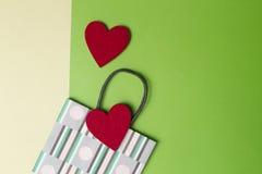 Kolorowy torba na zakupy i dwa czerwonego serca na greenery, kolor żółty barwiący papierowy tło Odgórny widok Odbitkowa przestrze Obrazy Royalty Free