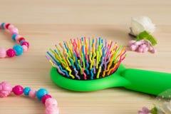 Kolorowy włosy grępli grzebień szczotkuje z rękojeścią, jaskrawi koraliki na wo Fotografia Stock