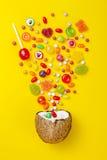 Kolorowy wybuch cukierki w koksie na kolor żółty barwiącym tle, kreatywnie życie wciąż, mieszkanie nieatutowy styl Fotografia Royalty Free