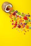 Kolorowy wybuch cukierki w koksie na kolor żółty barwiącym tle, kreatywnie życie wciąż, mieszkanie nieatutowy styl Obrazy Stock