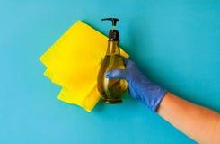 Koloru żółtego łachman dla czyścić dom trzyma żeńską ręką w błękitnej rękawiczce na błękitnym tle, naturalne światło, kopia space Zdjęcie Stock