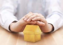 Koloru żółtego dom ochraniający rękami obraz stock