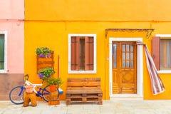 Koloru żółtego dom z kwiatami, ławką i bicyklem, Kolorowi domy w Burano wyspie blisko Wenecja, Włochy Wenecja pocztówka Sławny mi Zdjęcie Stock