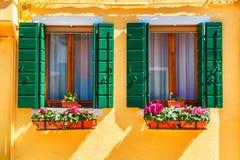 Koloru żółtego okno z zielonymi żaluzjami i dom Zdjęcie Royalty Free