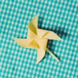 Koloru żółtego papierowy pinwheel na błękitnym tkaniny tle Zdjęcie Royalty Free