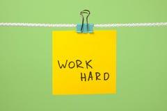 """Koloru żółtego papieru notatka na sznurku z teksta """"Work Hard† Fotografia Royalty Free"""
