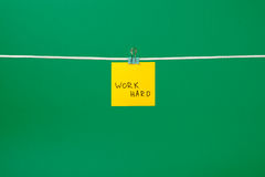 """Koloru żółtego papieru notatka na sznurku z teksta """"Work Hard† Zdjęcie Royalty Free"""