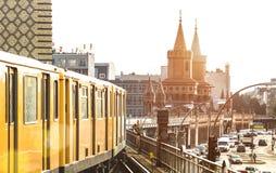 Koloru żółtego pociąg w Berlin, U-Bahn kolei z Oberbaum mostem na tle przy Friedrichshain Kreuzberg - zdjęcie stock