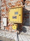 Koloru żółtego pudełko benzynowy metr i dystrybutor na wyścielanej ścianie z cegieł bez tynku Energetyczny sytem transportu Niebe zdjęcie stock