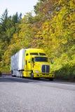 Koloru żółtego semi ciężarówka i reefer przyczepa jedzie ciężką jesieni drogę fotografia royalty free