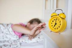 Koloru żółtego zegar jest na stołowym przedstawień siedem o ` zegarze dziecko w wieku szkolnym budzi się up i obraca daleko alarm fotografia stock