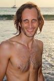 Koloru portreta fotografia przystojnego mężczyzna przyglądający up i ono uśmiecha się podczas dnia przy plażą Obraz Royalty Free