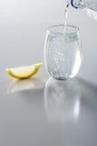 Kolsyrat vatten i exponeringsglas som hälls Arkivbild