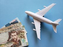 kolumbianische Banknoten, weißes Plastikflugzeug und blauer Hintergrund lizenzfreie stockfotos