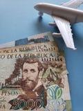 kolumbianische Banknoten, weißes Plastikflugzeug und blauer Hintergrund stockfoto