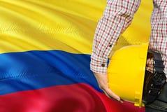 Kolumbijski inżynier trzyma żółtego zbawczego hełm z machać Kolumbia chorągwianego tło Budowy i budynku poj?cie fotografia royalty free