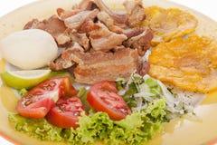 Kolumbijski jedzenie, smażący chicharron towarzyszący sałatką, patacon i arepa, zdjęcia stock