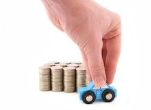 Kolumny monety i ręka z samochodem Zdjęcia Stock