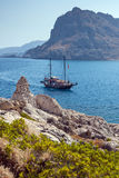 Kolymbia beach with the rocky coast with boat. Stock Images