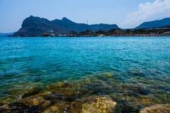 Kolymbia strand med den steniga kusten Royaltyfria Foton