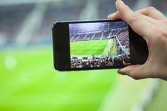 Komórkowego telefonu ekran z stadionu futbolowego polem z drużynami bawić się dopasowanie Obraz Royalty Free
