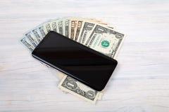 Komórkowy telefon i amerykanina dolarowy pieniądze na bielu zdjęcia royalty free