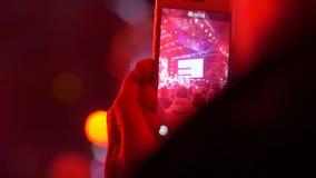 Komórkowy telefon w rękach strzela scenę w światło reflektorów i tłumu ludzie w wieczór na koncercie zbiory wideo