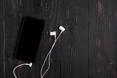 Komórkowy z słuchawkami na drewnianym tle Zdjęcie Stock