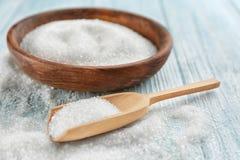 Kom en lepel met suiker op houten lijst, Stock Fotografie