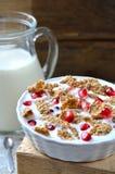 Kom melk met graangewassen en granaatappelzaden Stock Fotografie
