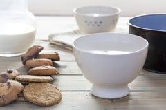 Kom melk met koekjes en een steelpan aan hitte royalty-vrije stock foto