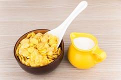 Kom met cornflakes en kruik melk op lijst Stock Foto