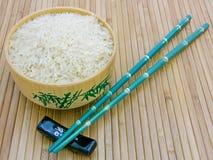 Kom met rijst, eetstokjes op bamboemat Royalty-vrije Stock Afbeeldingen
