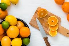 Kom met verschillende types van gehele citrusvruchten: sinaasappelen, grapefruits, kalk en citroenen, en houten raad met plakken  Royalty-vrije Stock Foto