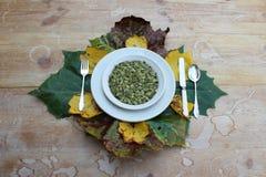 Kom pompoenzaden door de herfstbladeren dat worden omringd Stock Afbeelding