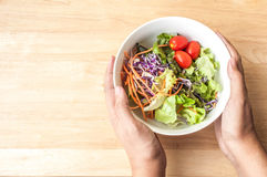 kom van de hand de greep gemengde Salade op houten lijst Stock Foto