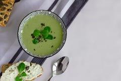 Kom van de soep van de broccoliroom, korrelbrood met pompoenzaden en lepel op de lijst, gezond vegetarisch het eten concept Evenw stock afbeeldingen