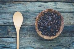 Kom van geroosterde koffiebonen en een lepel op zeer oud en rustiek Stock Afbeeldingen