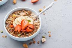 Kom van granola of muesli met aardbei, banaan en melk stock afbeelding